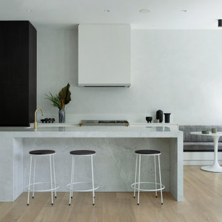 Contemporary galley eat-in kitchen in Perth with flat-panel cabinets, white cabinets, light hardwood floors, with island, beige floor and grey benchtop.