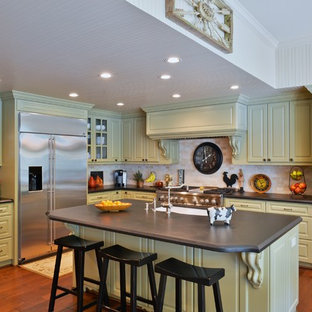 Large traditional open concept kitchen appliance - Example of a large classic l-shaped open concept kitchen design in Houston with an undermount sink, raised-panel cabinets, green cabinets, granite countertops, beige backsplash, stone tile backsplash, stainless steel appliances and an island