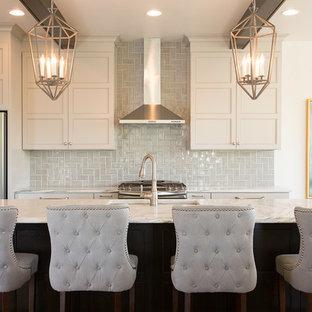 Klassische Küche mit Unterbauwaschbecken, Schrankfronten mit vertiefter Füllung, beigen Schränken, Küchenrückwand in Blau, Rückwand aus Keramikfliesen, Küchengeräten aus Edelstahl, dunklem Holzboden und Kücheninsel in Milwaukee