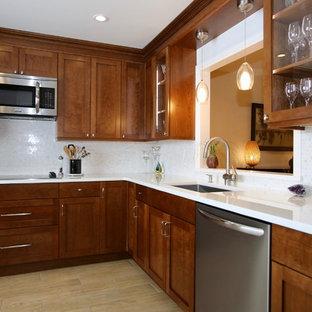 ニューヨークの中サイズのエクレクティックスタイルのおしゃれなキッチン (アンダーカウンターシンク、シェーカースタイル扉のキャビネット、濃色木目調キャビネット、クオーツストーンカウンター、白いキッチンパネル、大理石の床、シルバーの調理設備の、磁器タイルの床、アイランドなし、ベージュの床、白いキッチンカウンター) の写真