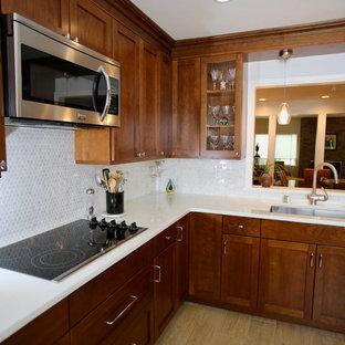 ニューヨークの中サイズのエクレクティックスタイルのおしゃれなキッチン (アンダーカウンターシンク、シェーカースタイル扉のキャビネット、濃色木目調キャビネット、クオーツストーンカウンター、白いキッチンパネル、大理石のキッチンパネル、シルバーの調理設備、磁器タイルの床、アイランドなし、ベージュの床、白いキッチンカウンター) の写真