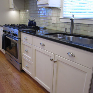 Inspiration for a transitional single-wall eat-in kitchen remodel in Bridgeport with an undermount sink, recessed-panel cabinets, white cabinets, granite countertops, green backsplash, subway tile backsplash and stainless steel appliances