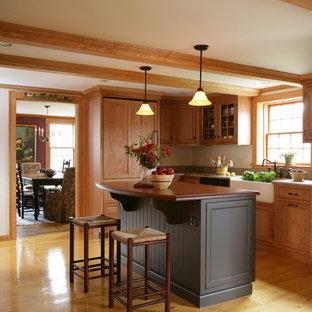 Geschlossene, Mittelgroße Urige Küche mit Landhausspüle, Arbeitsplatte aus Holz, hellen Holzschränken, Elektrogeräten mit Frontblende, hellem Holzboden, Kücheninsel, beigem Boden und brauner Arbeitsplatte in Boston