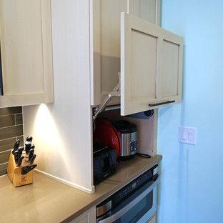 ボストンの中サイズのエクレクティックスタイルのおしゃれなキッチン (エプロンフロントシンク、シェーカースタイル扉のキャビネット、ベージュのキャビネット、クオーツストーンカウンター、メタリックのキッチンパネル、ガラスタイルのキッチンパネル、シルバーの調理設備の、無垢フローリング) の写真
