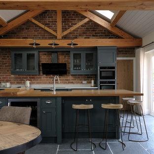チェシャーの中サイズのラスティックスタイルのおしゃれなキッチン (シェーカースタイル扉のキャビネット、レンガのキッチンパネル、シルバーの調理設備の、黒い床) の写真