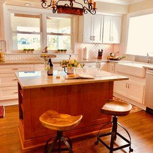 Mittelgroße Landhausstil Wohnküche in L-Form mit Landhausspüle, Glasfronten, weißen Schränken, Granit-Arbeitsplatte, Küchenrückwand in Weiß, Rückwand aus Porzellanfliesen, Küchengeräten aus Edelstahl, dunklem Holzboden, Kücheninsel, braunem Boden und grüner Arbeitsplatte in Sonstige