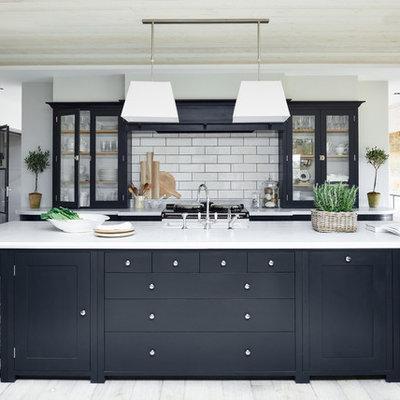 Transitional kitchen photo in London with glass-front cabinets, white backsplash, subway tile backsplash and an island