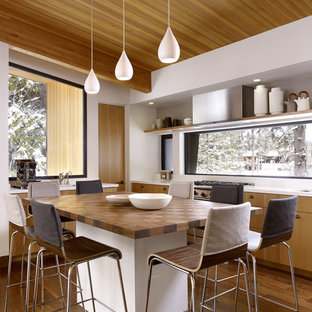 Inspiration for a midcentury eat-in kitchen in Sacramento with wood benchtops, flat-panel cabinets and medium wood cabinets.