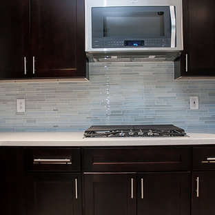 This is an example of a large modern l-shaped eat-in kitchen in Houston with shaker cabinets, dark wood cabinets, blue splashback, mosaic tile splashback, stainless steel appliances, with island, a double-bowl sink, quartz benchtops, porcelain floors, grey floor and white benchtop.
