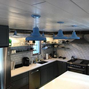 ポートランド(メイン)の大きいインダストリアルスタイルのおしゃれなキッチン (アンダーカウンターシンク、シェーカースタイル扉のキャビネット、グレーのキャビネット、クオーツストーンカウンター、白いキッチンパネル、セラミックタイルのキッチンパネル、カラー調理設備、クッションフロア) の写真