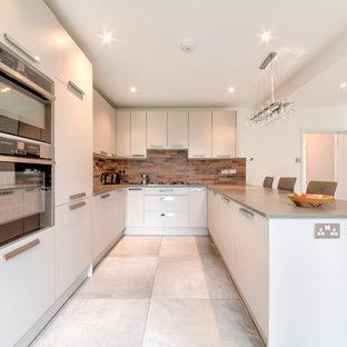 ロンドンの広いモダンスタイルのおしゃれなキッチン (エプロンフロントシンク、フラットパネル扉のキャビネット、白いキャビネット、ラミネートカウンター、マルチカラーのキッチンパネル、レンガのキッチンパネル、シルバーの調理設備、セラミックタイルの床、グレーの床、グレーのキッチンカウンター) の写真