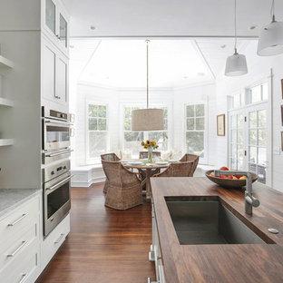 Foto de cocina comedor costera con fregadero de un seno, armarios estilo shaker, puertas de armario blancas, encimera de madera y electrodomésticos de acero inoxidable