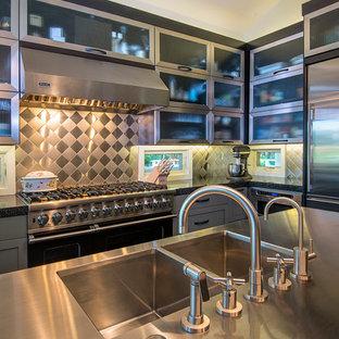 Inredning av ett modernt litet kök, med en undermonterad diskho, luckor med glaspanel, skåp i rostfritt stål, bänkskiva i rostfritt stål, stänkskydd med metallisk yta, stänkskydd i metallkakel, rostfria vitvaror, mörkt trägolv och en köksö
