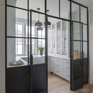 Medium sized coastal u-shaped kitchen pantry in Charleston with a belfast sink, flat-panel cabinets, white cabinets, light hardwood flooring, no island, beige floors and white worktops.