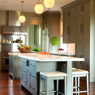 Design ideas for a tropical kitchen in Charleston with shaker cabinets, green cabinets, metallic splashback, medium hardwood floors, multiple islands, brown floor and white benchtop.