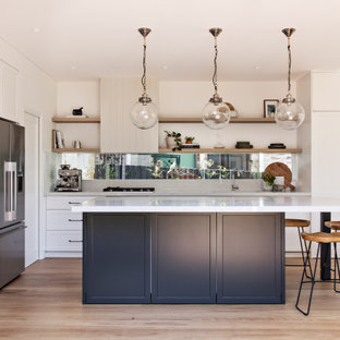 Photo of a beach style l-shaped kitchen in Newcastle - Maitland with an undermount sink, shaker cabinets, white cabinets, white splashback, stainless steel appliances, light hardwood floors, with island, beige floor and white benchtop.