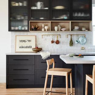 Mittelgroße Mid-Century Wohnküche in L-Form mit Landhausspüle, Schrankfronten im Shaker-Stil, schwarzen Schränken, Marmor-Arbeitsplatte, Küchenrückwand in Grau, Rückwand aus Keramikfliesen, Küchengeräten aus Edelstahl, hellem Holzboden, Kücheninsel, braunem Boden und grauer Arbeitsplatte in Sydney
