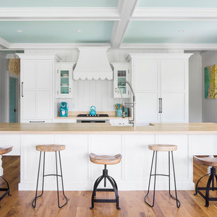 Mid-sized beach style open concept kitchen designs - Mid-sized coastal galley medium tone wood floor open concept kitchen photo in Boston with white cabinets, wood countertops, white backsplash, an island, paneled appliances, a farmhouse sink and shaker cabinets