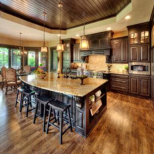 Große, Zweizeilige Mediterrane Küche mit Unterbauwaschbecken, profilierten Schrankfronten, dunklen Holzschränken, Granit-Arbeitsplatte, Küchenrückwand in Beige, Küchengeräten aus Edelstahl und Kücheninsel in Kansas City