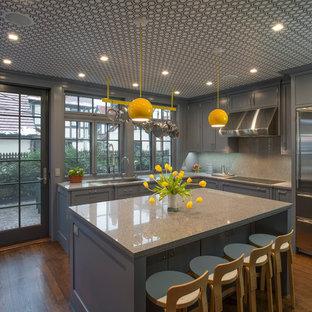 Diseño de cocina en U, actual, grande, con armarios con paneles empotrados, puertas de armario azules, encimera de cuarzo compacto, una isla, fregadero bajoencimera y suelo de madera en tonos medios