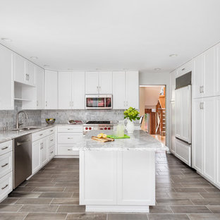 Large beach style l-shaped eat-in kitchen in Other with a single-bowl sink, shaker cabinets, white cabinets, quartzite benchtops, grey splashback, marble splashback, panelled appliances, ceramic floors, with island, grey floor and grey benchtop.
