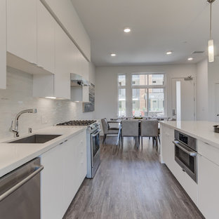 Open concept kitchen appliance - Example of a single-wall open concept kitchen design in San Francisco with an undermount sink, flat-panel cabinets, white cabinets, stainless steel appliances, an island and white countertops