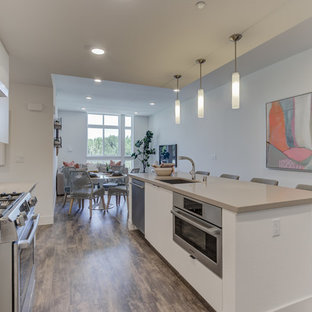 Open concept kitchen appliance - L-shaped open concept kitchen photo in San Francisco with an undermount sink, flat-panel cabinets, white cabinets, stainless steel appliances, an island and white countertops