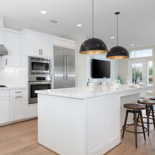 Open concept kitchen designs - Example of a l-shaped open concept kitchen design in San Francisco with an undermount sink, white cabinets, gray backsplash, stainless steel appliances, an island and recessed-panel cabinets