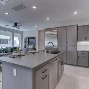 Open concept kitchen appliance - L-shaped open concept kitchen photo in San Francisco with an undermount sink, recessed-panel cabinets, gray cabinets, stainless steel appliances and an island