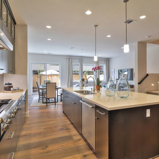 Open concept kitchen ideas - Inspiration for a l-shaped medium tone wood floor open concept kitchen remodel in San Francisco with an undermount sink, flat-panel cabinets, dark wood cabinets, stainless steel appliances and an island