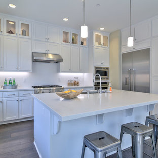 Open concept kitchen inspiration - Inspiration for a l-shaped dark wood floor open concept kitchen remodel in San Francisco with an undermount sink, shaker cabinets, white cabinets, stainless steel appliances and an island