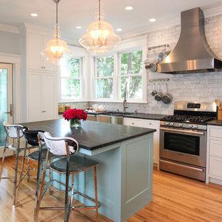 ミネアポリスの中サイズのエクレクティックスタイルのおしゃれなキッチン (ダブルシンク、フラットパネル扉のキャビネット、白いキャビネット、ソープストーンカウンター、グレーのキッチンパネル、大理石のキッチンパネル、シルバーの調理設備、無垢フローリング) の写真