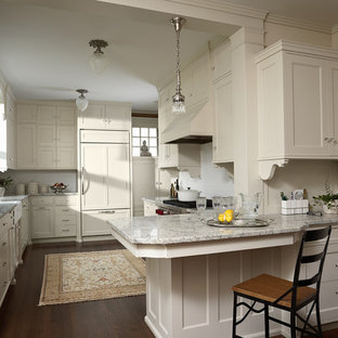 This is an example of a mid-sized traditional u-shaped eat-in kitchen in Minneapolis with a farmhouse sink, recessed-panel cabinets, white cabinets, granite benchtops, white splashback, ceramic splashback, panelled appliances, dark hardwood floors, a peninsula and brown floor.