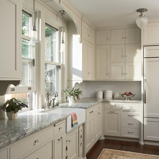 Design ideas for a mid-sized victorian u-shaped kitchen in Minneapolis with a farmhouse sink, recessed-panel cabinets, white cabinets, granite benchtops, white splashback, ceramic splashback, panelled appliances, dark hardwood floors, a peninsula and brown floor.