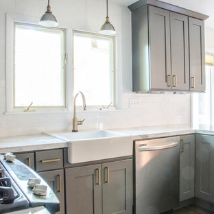 This is an example of a mid-sized midcentury u-shaped eat-in kitchen in Other with a farmhouse sink, shaker cabinets, grey cabinets, laminate benchtops, white splashback, subway tile splashback, stainless steel appliances, medium hardwood floors and a peninsula.