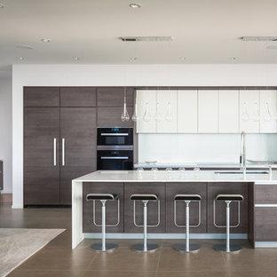 シアトルの大きいコンテンポラリースタイルのおしゃれなキッチン (アンダーカウンターシンク、フラットパネル扉のキャビネット、クオーツストーンカウンター、白いキッチンパネル、パネルと同色の調理設備、セラミックタイルの床、白いキャビネット) の写真