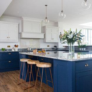 Immagine di una cucina a L classica di medie dimensioni con ante a filo, ante blu, top in granito, paraspruzzi con lastra di vetro, isola e pavimento in legno massello medio