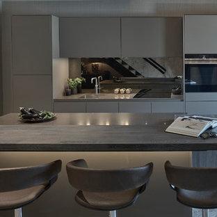 Immagine di una cucina contemporanea chiusa e di medie dimensioni con lavello da incasso, ante lisce, ante marroni, top in granito, paraspruzzi marrone, paraspruzzi a specchio, elettrodomestici neri, pavimento in gres porcellanato, isola e pavimento marrone