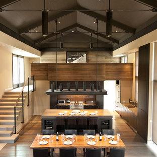 Foto de cocina actual, abierta, con armarios con paneles lisos, puertas de armario de madera en tonos medios, salpicadero marrón y salpicadero de vidrio templado