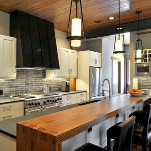 Idee per una cucina a L chic con elettrodomestici in acciaio inossidabile, top in legno, paraspruzzi nero, isola, lavello a vasca singola e parquet scuro
