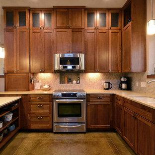 オースティンの中くらいのサンタフェスタイルのおしゃれなキッチン (アンダーカウンターシンク、シェーカースタイル扉のキャビネット、濃色木目調キャビネット、コンクリートカウンター、ベージュキッチンパネル、石タイルのキッチンパネル、シルバーの調理設備、コンクリートの床) の写真