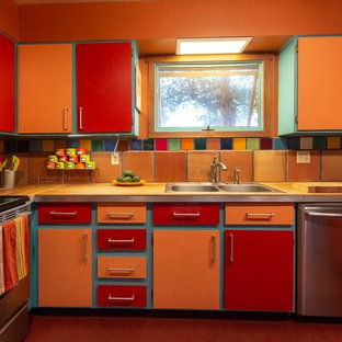 Inspiration for a kitchen in Other with a drop-in sink, flat-panel cabinets, orange cabinets, wood benchtops, multi-coloured splashback, terra-cotta splashback, stainless steel appliances, linoleum floors, red floor and brown benchtop.