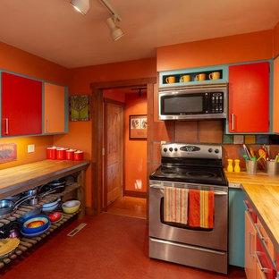他の地域のサンタフェスタイルのおしゃれなキッチン (ドロップインシンク、フラットパネル扉のキャビネット、オレンジのキャビネット、木材カウンター、マルチカラーのキッチンパネル、テラコッタタイルのキッチンパネル、シルバーの調理設備、リノリウムの床、赤い床、茶色いキッチンカウンター) の写真