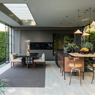 Imagen de cocina lineal, de estilo zen, de tamaño medio, con armarios con paneles lisos, puertas de armario grises, una isla, suelo beige y encimeras negras
