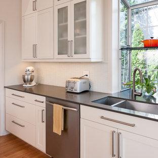 Exempel på ett mellanstort modernt kök, med en dubbel diskho, skåp i shakerstil, gula skåp, marmorbänkskiva, vitt stänkskydd, stänkskydd i glaskakel, rostfria vitvaror, ljust trägolv och en köksö