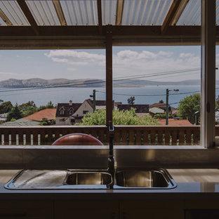 Kolonialstil Küche mit gelben Schränken und Kücheninsel in Hobart