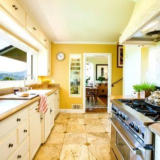 サンフランシスコの中サイズのトラディショナルスタイルのおしゃれなキッチン (エプロンフロントシンク、シェーカースタイル扉のキャビネット、ベージュのキャビネット、御影石カウンター、黄色いキッチンパネル、シルバーの調理設備の、ライムストーンの床) の写真