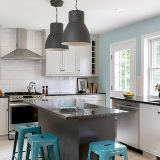 Medium sized classic kitchen in New York with recessed-panel cabinets, granite worktops, white splashback, stainless steel appliances, ceramic flooring, an island, white floors, black worktops, a submerged sink, metro tiled splashback and grey cabinets.