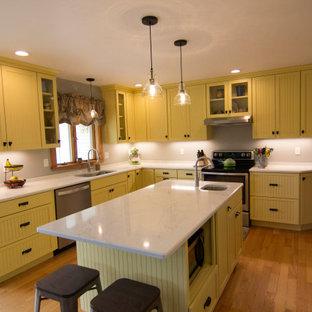 Esempio di una cucina country di medie dimensioni con lavello sottopiano, ante con riquadro incassato, ante gialle, top in quarzo composito, paraspruzzi grigio, elettrodomestici in acciaio inossidabile, parquet chiaro, isola, pavimento arancione e top bianco