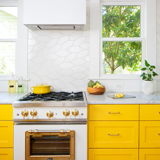 Design ideas for a mid-sized eclectic l-shaped eat-in kitchen in Austin with an undermount sink, recessed-panel cabinets, yellow cabinets, marble benchtops, white splashback, ceramic splashback, white appliances, medium hardwood floors, with island, brown floor and white benchtop.